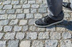 Pieds masculins dans les jeans gris et des espadrilles se tenant sur le vieux trottoir en pierre Images stock