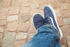 Pieds masculins de détente dans des chaussures sportives de toile bleue Photo libre de droits
