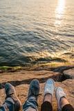 Pieds masculins et femelles dans des espadrilles sur le rivage rocheux avec la belle vue sur l'eau onduleuse, l'amitié ou le conc Photos libres de droits
