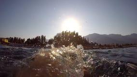 Pieds masculins nageant sur l'eau en mer Point de vue de jeune homme se trouvant sur l'eau et des secousses ses jambes Fin de mou banque de vidéos