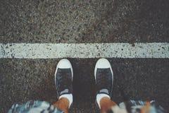 Pieds masculins près de la ligne blanche sur l'asphalte Images libres de droits