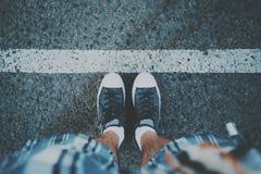 Pieds masculins près de la ligne blanche sur l'asphalte Photos stock