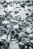 Pieds masculins sur la côte rocheuse, bleu modifié la tonalité Image libre de droits