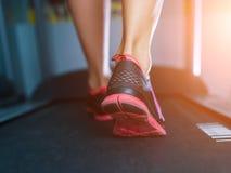 Pieds musculaires femelles dans des espadrilles fonctionnant sur le tapis roulant au gymnase Concept pour la forme physique, l'ex Image libre de droits