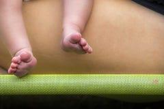 Pieds nouveau-nés avec le fond de jambe de mère sur la barre verte image stock