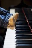 Pieds nouveau-nés d'enfant essayant de jouer le piano photo stock