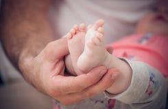 Pieds nouveau-nés de bébé dans des mains masculines Photographie stock
