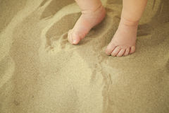 Pieds nouveau-nés de bébé jouant dans le sable photographie stock