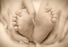 Pieds nouveau-nés de bébé sur les mains femelles Photographie stock libre de droits