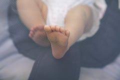 Pieds nouveau-nés poussant une moustiquaire photographie stock