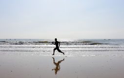 Pieds nus d'homme courant sur la plage Photographie stock