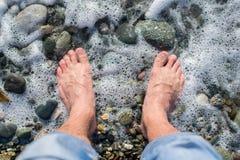 Pieds nus d'un homme qui se tient sur un Pebble Beach à côté de la vague de mer L'eau écume Photos libres de droits