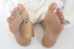 Pieds nus dans le lit avec l'étiquette en bois image stock