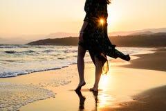 Pieds nus de femme dans la robe verte sur la plage avant le coucher du soleil orange, silhouette avec des rayons Images libres de droits