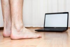 Pieds nus et ordinateur portatif sur l'étage Image libre de droits