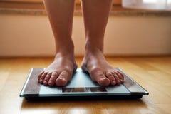 Pieds nus femelles avec l'échelle de poids images stock