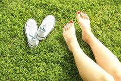 Pieds nus femelles sur l'herbe mawed de pelouse La jeune femme se reposant dehors nu-pieds, prennent un concept de coupure Étudia Image libre de droits