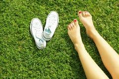 Pieds nus femelles sur l'herbe mawed de pelouse La jeune femme se reposant dehors nu-pieds, prennent un concept de coupure Étudia Image stock