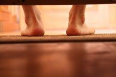 Pieds nus masculins de photo de dessous le lit Images stock