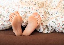 Pieds nus sous la couverture Photographie stock