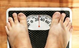 Pieds obèses sur l'échelle Photos stock