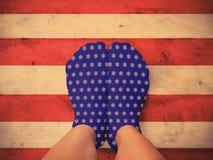 Pieds portant les chaussettes bleues avec la forme blanche d'étoile sur le plancher en bois Images stock
