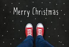 Pieds portant les chaussures rouges sur le fond noir Photos libres de droits