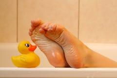Pieds prenant avec le canard de bain image stock
