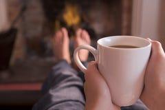 Pieds réchauffant à la cheminée avec du café photographie stock