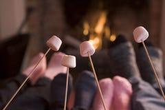 Pieds réchauffant à une cheminée avec des guimauves Image stock
