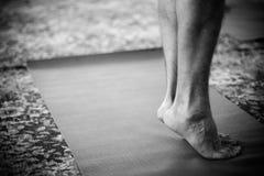 Pieds restant sur le couvre-tapis de yoga Photographie stock