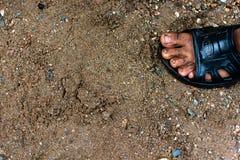 Pieds sales et nus du ` s d'enfant sur le gravier - pauvres personnes et PO humain Photos stock
