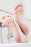 Pieds sur le bord d'une baignoire Image libre de droits