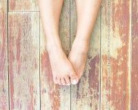 Pieds sur un plancher en bois Photographie stock