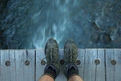 Pieds sur un pont en bois avec de l'eau l'écoulement de l'eau - vers le bas ci-dessous Photo libre de droits