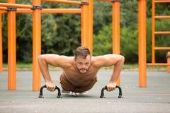 Piegamenti sulle braccia di addestramento del modello di forma fisica dell'uomo all'aperto Immagini Stock