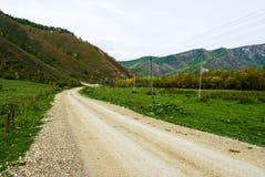 Piegamento di una strada non asfaltata nelle montagne Fotografia Stock Libera da Diritti