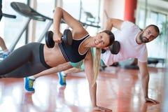 Piegamento sulle braccia di forza di flessione dell'uomo e della donna della palestra con la testa di legno in un allenamento Fotografie Stock