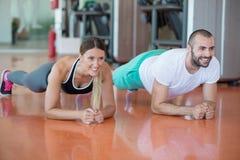 Piegamento sulle braccia di forza di flessione dell'uomo e della donna della palestra con la testa di legno in un allenamento Immagine Stock