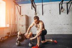 Piegamento sulle braccia di forza di flessione dell'uomo e della donna dell'istruttore in un allenamento di forma fisica Fotografia Stock