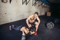 Piegamento sulle braccia di forza di flessione dell'uomo e della donna dell'istruttore in un allenamento di forma fisica Immagini Stock Libere da Diritti