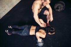 Piegamento sulle braccia di forza di flessione dell'uomo e della donna dell'istruttore in un allenamento di forma fisica Fotografia Stock Libera da Diritti