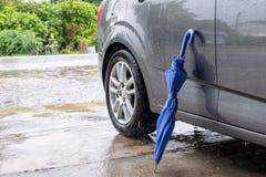 Piegatura blu vicina dell'ombrello con l'automobile grigia fotografia stock