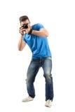Pieghi o penda il giovane che prende la foto con dslr Fotografia Stock