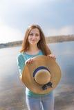 Piegowaty szczęśliwy dziewczyny mienia kapelusz i patrzeć kamerę fotografia stock