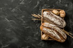 Piekarnia - nieociosani skorupiaści bochenki chleb i babeczki na czerni zdjęcie royalty free