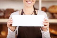 Piekarnia pracownik trzyma up pustego znaka Obrazy Stock