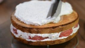 Piekarnia szef kuchni dekoruje tort z ?mietank? Poj?cie piekarnia, kawiarnia, piekarnia biznes i przemys? robi? tortowi i, dlacze zbiory