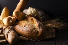 Piekarnia - złociści nieociosani skorupiaści bochenki chleb i babeczki na czarnym tle obraz stock