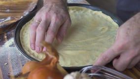 Piekarniane ręki stawia ciasto dla kulebiaka w wypiekowej tacy zamkniętej w górę Pizza producent robi ciastu dla włoskiej pizzy p zbiory wideo